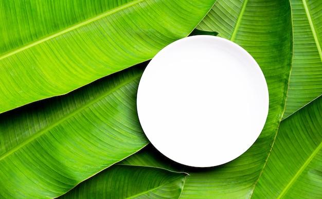Assiette en céramique blanche vide sur fond de feuilles de bananier. vue de dessus