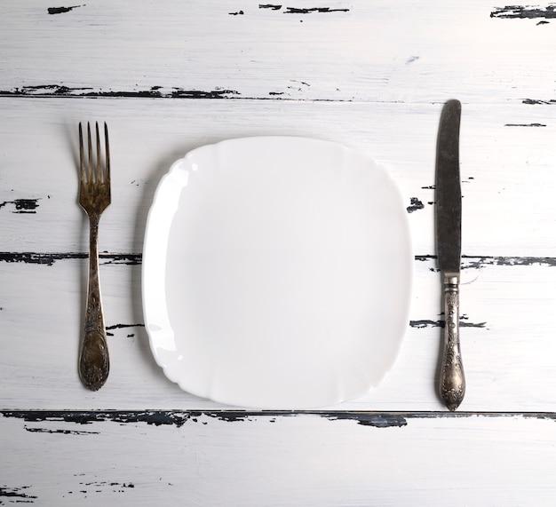Assiette en céramique blanche vide avec une fourchette et un couteau