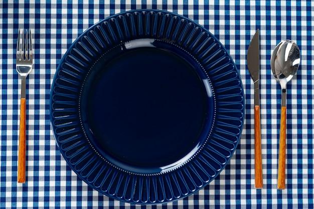Assiette en céramique bleu profond avec des couverts close up on table