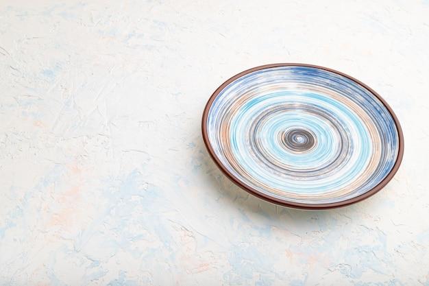 Assiette en céramique bleue vide sur fond de béton blanc. vue de côté,
