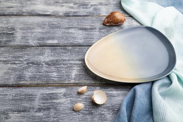 Assiette en céramique bleue vide sur fond en bois gris et textile bleu. vue de côté,