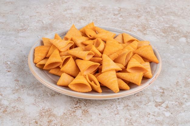Assiette en céramique de chips triangulaires croquantes sur marbre.