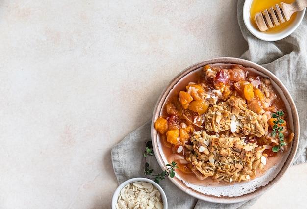 Assiette en céramique avec un délicieux crumble aux prunes servi avec de la glace à la vanille et des herbes