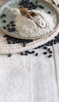 Assiette en céramique avec de la farine de haricots noirs et des haricots secs avec une cuillère en bois en gros plan. alimentation saine et concept végétarien. ingrédient traditionnel de cousin d'amérique latine