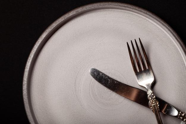 Assiette en céramique grise ronde vide sur fond noir avec fourchette et couteau en cupronickel vintage