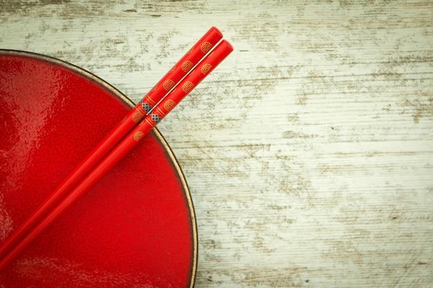 Assiette en céramique orientale et baguettes en rouge