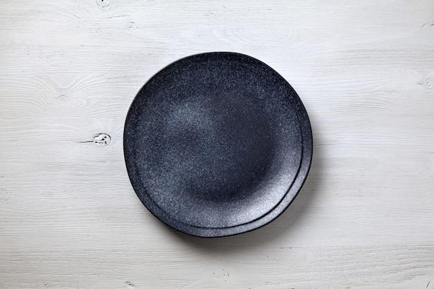 Assiette en céramique sombre sur fond de bois blanc