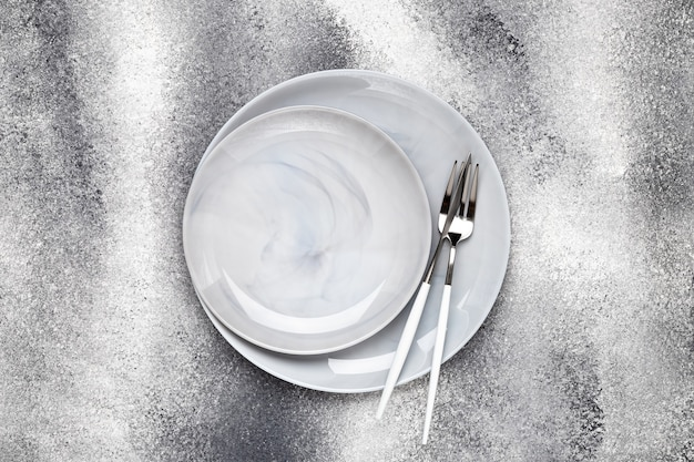 Assiette en céramique vide et couteau inutilisé avec fourchette, couverts sur table grise, concept de service. conception à plat. le menu du restaurant. carte de voeux, mise en page, maquette avec espace de copie. vue de dessus. modèle.