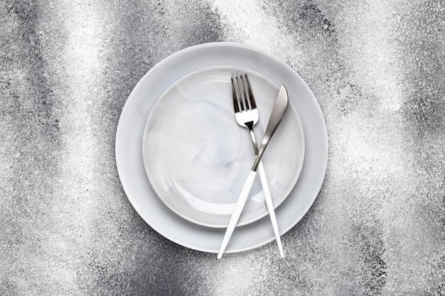 Assiette en céramique vide et couteau inutilisé avec fourchette, couverts sur table grise, concept de service. conception à plat. le menu du restaurant. carte de voeux, mise en page, maquette avec espace de copie. vue de dessus.