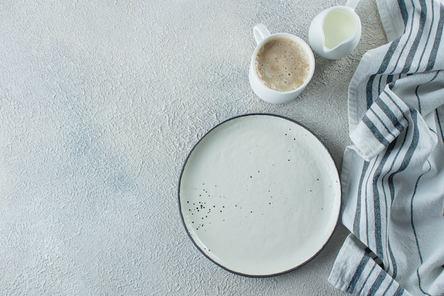 Assiette en céramique vide, tasse de café et serviette de cuisine rayée
