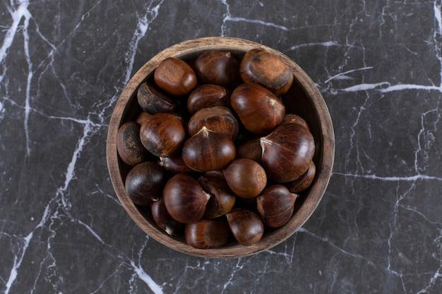 Assiette de châtaignes comestibles grillées posées sur du marbre.