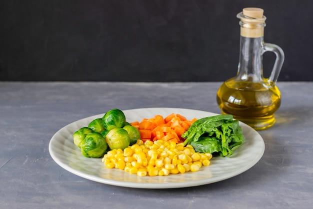 Assiette avec chou, carottes, maïs et épinards