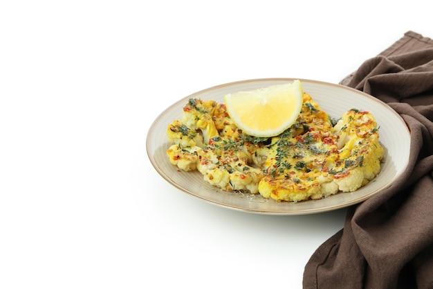 Assiette avec chou-fleur cuit au four et torchon isolé sur fond blanc.