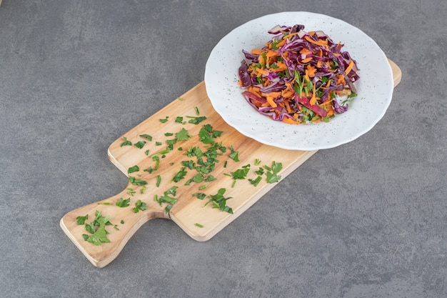 Assiette de chou haché et carottes sur planche de bois. photo de haute qualité