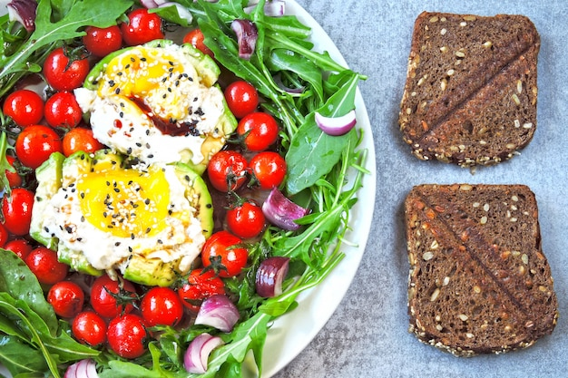 Assiette colorée avec des aliments sains. salade de roquette, avocat, oeuf et tomates cerises.
