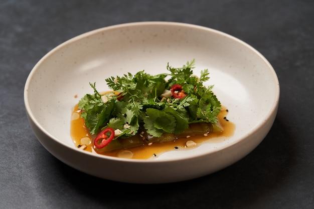 Assiette de concombres écrasés avec persil à l'ail et huile végétale de piment rouge