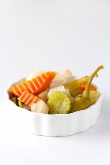Assiette de cornichons, carottes de légumes, chili, radis dans un bol en céramique blanche.