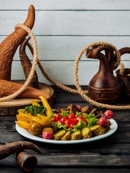Assiette avec des cornichons sur une table en bois