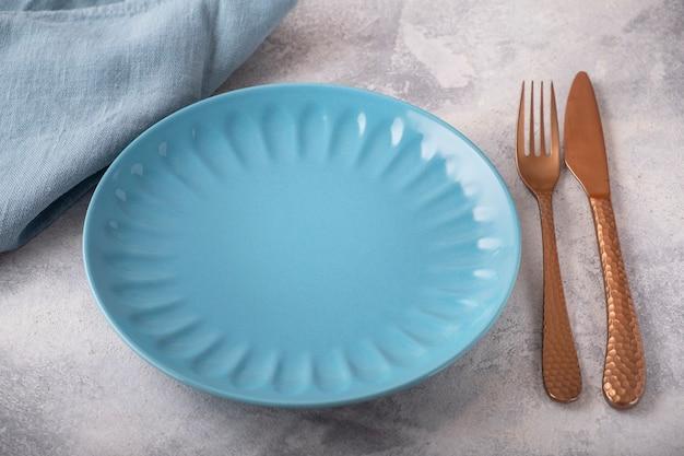 Assiette de couleur vide servie avec fourchette, couteau et serviette
