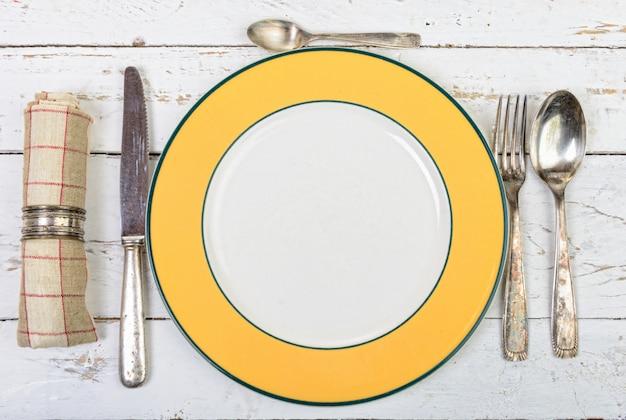 Assiette avec des couverts en argent sur une vieille table blanche