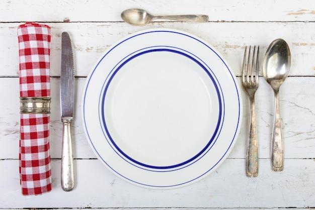 Assiette avec des couverts en argent sur une vieille table