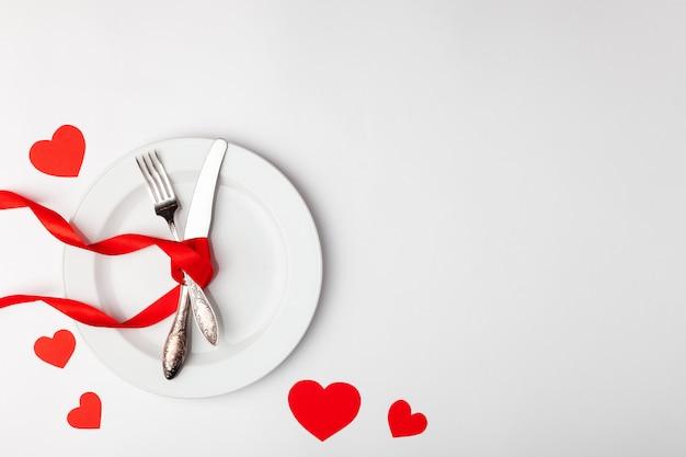 Assiette et couverts attachés avec un ruban rouge