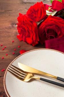 Assiette, couverts et roses, concept de dîner romantique. photo verticale