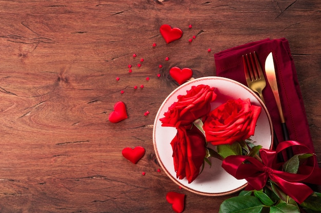 Assiette, couverts et roses, concept de dîner romantique