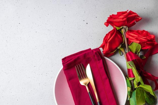 Assiette, couverts et roses rouges, concept de dîner romantique.
