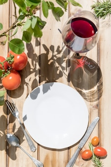 Assiette, couverts, verre de vin rouge et tomates sur une table en bois