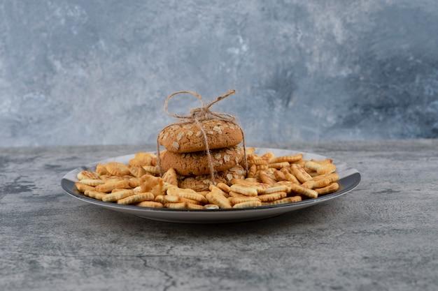 Assiette avec craquelins salés et biscuits à l'avoine sur fond de marbre.