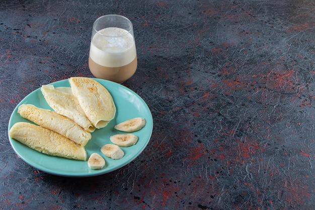 Assiette de crêpes et de bananes tranchées avec un verre de café au lait sur une surface sombre.