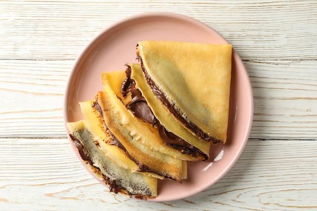 Assiette de crêpes à la pâte de chocolat sur fond de bois blanc