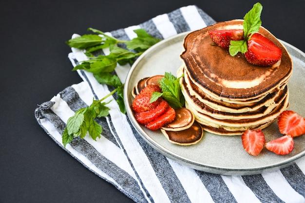 Assiette avec des crêpes traditionnelles et de minuscules céréales de crêpes aux fraises et feuilles de menthe sur fond sombre. nourriture à la mode. mini crêpes aux céréales