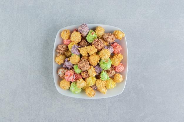 Une assiette creuse blanche de pop-corn multicolore sucré.