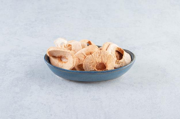 Une assiette creuse bleue avec des pommes séchées saines sur pierre.