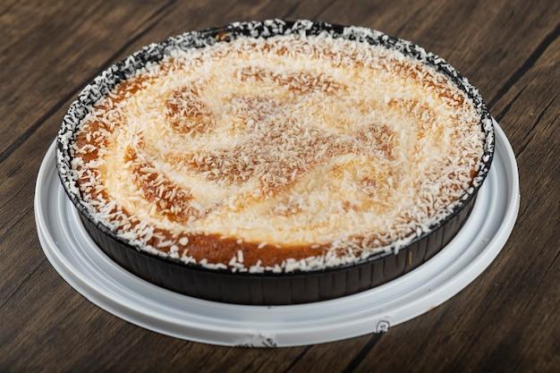 Assiette creuse avec une délicieuse tarte à la noix de coco sur une surface en bois