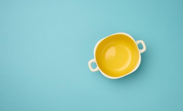 Assiette creuse jaune vide sur fond bleu, vue de dessus, espace pour copie