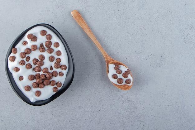 Une assiette creuse noire de lait avec des céréales au chocolat et une cuillère en bois. photo de haute qualité