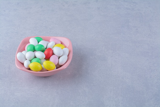 Une assiette creuse rose pleine de bonbons aux haricots colorés sur fond gris. photo de haute qualité