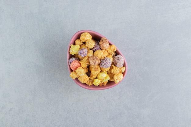 Une assiette creuse rose de pop-corn multicolore sucré.