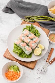 Assiette de crevettes roule sur une planche à découper avec asperges