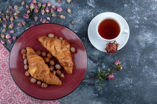 Assiette de croissants aux noisettes et tasse de thé noir sur marbre.
