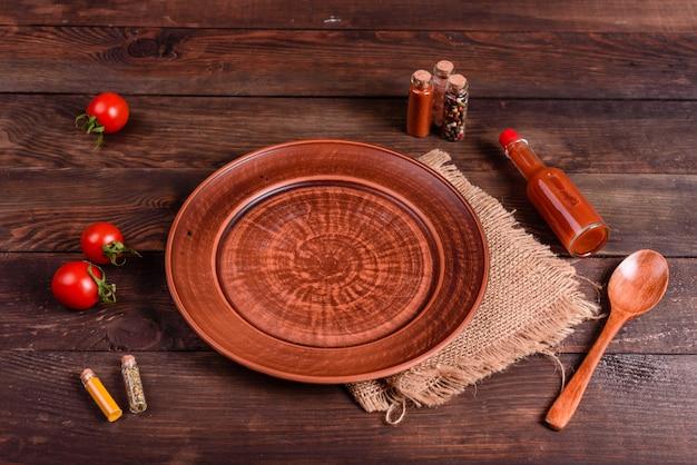 Assiette, cuillère, épices et autres accessoires de cuisine sur un fond en bois foncé