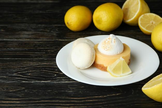 Assiette avec cupcake et macarons et citrons sur table en bois