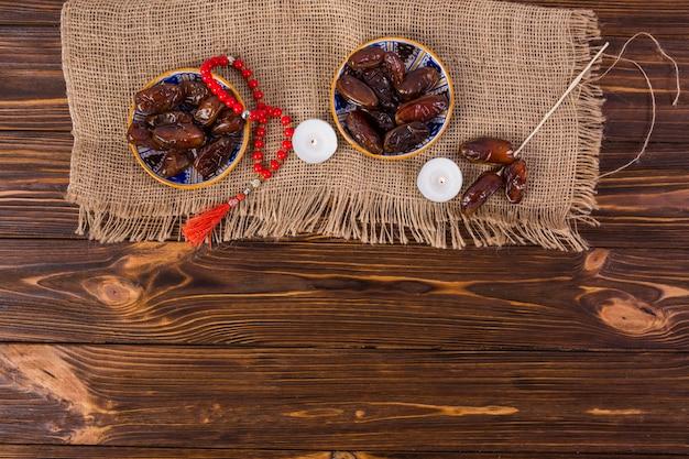 Assiette de dattes juteuses avec des perles de prière rouges et une bougie allumée sur un bureau en bois