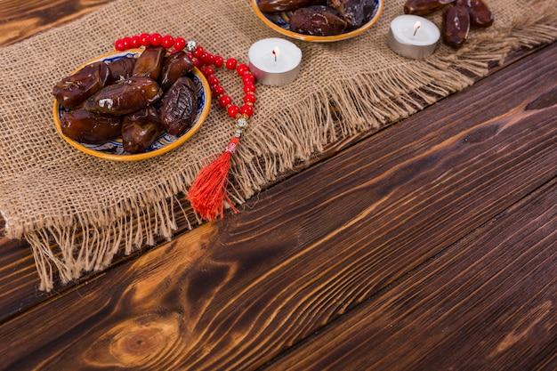 Assiette de dattes mûres et juteuses avec des perles de prière rouges avec des bougies allumées sur une nappe de jute sur le bureau en bois