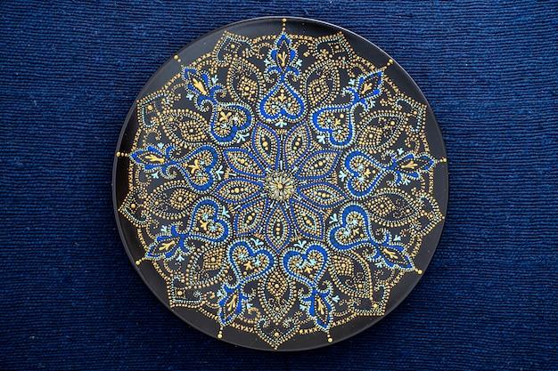 Assiette décorative en céramique aux couleurs noir, bleu et doré