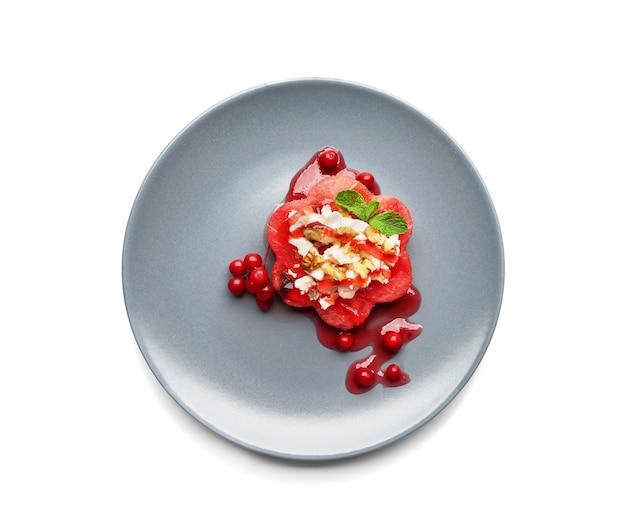 Assiette avec une délicieuse salade de pastèque sur une surface blanche