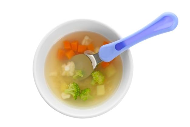 Assiette avec une délicieuse soupe de bébé sur fond blanc